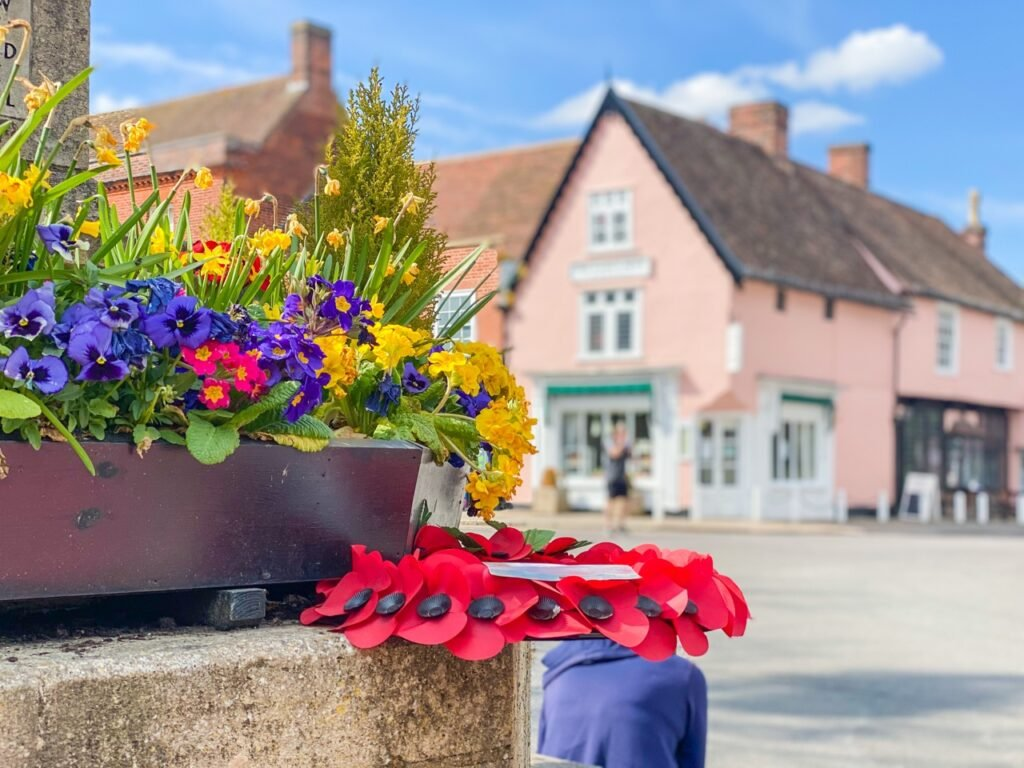 Dedham Village, close up of the flowers on Dedham Memorial monument with Tiptree Team Room The Essex Rose in the background